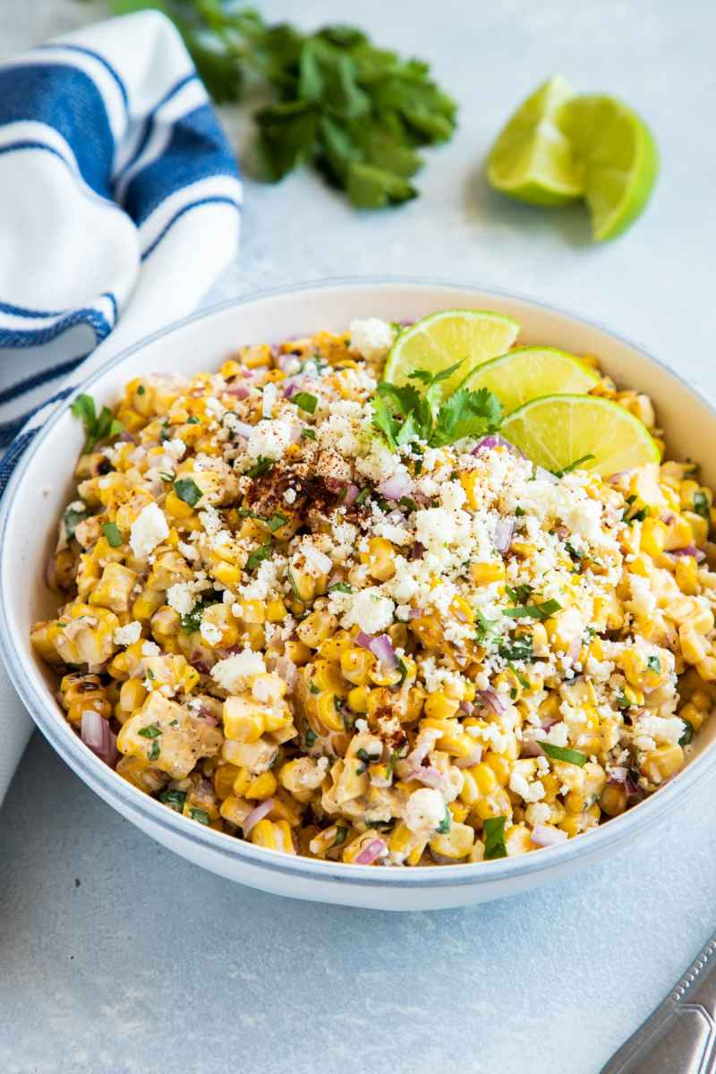 Mexican Grilled Corn salad served in a shallow bowl topped with cotija cheese, cilantro and lime slices.