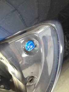 Blue plastic fastener viewed from side of car