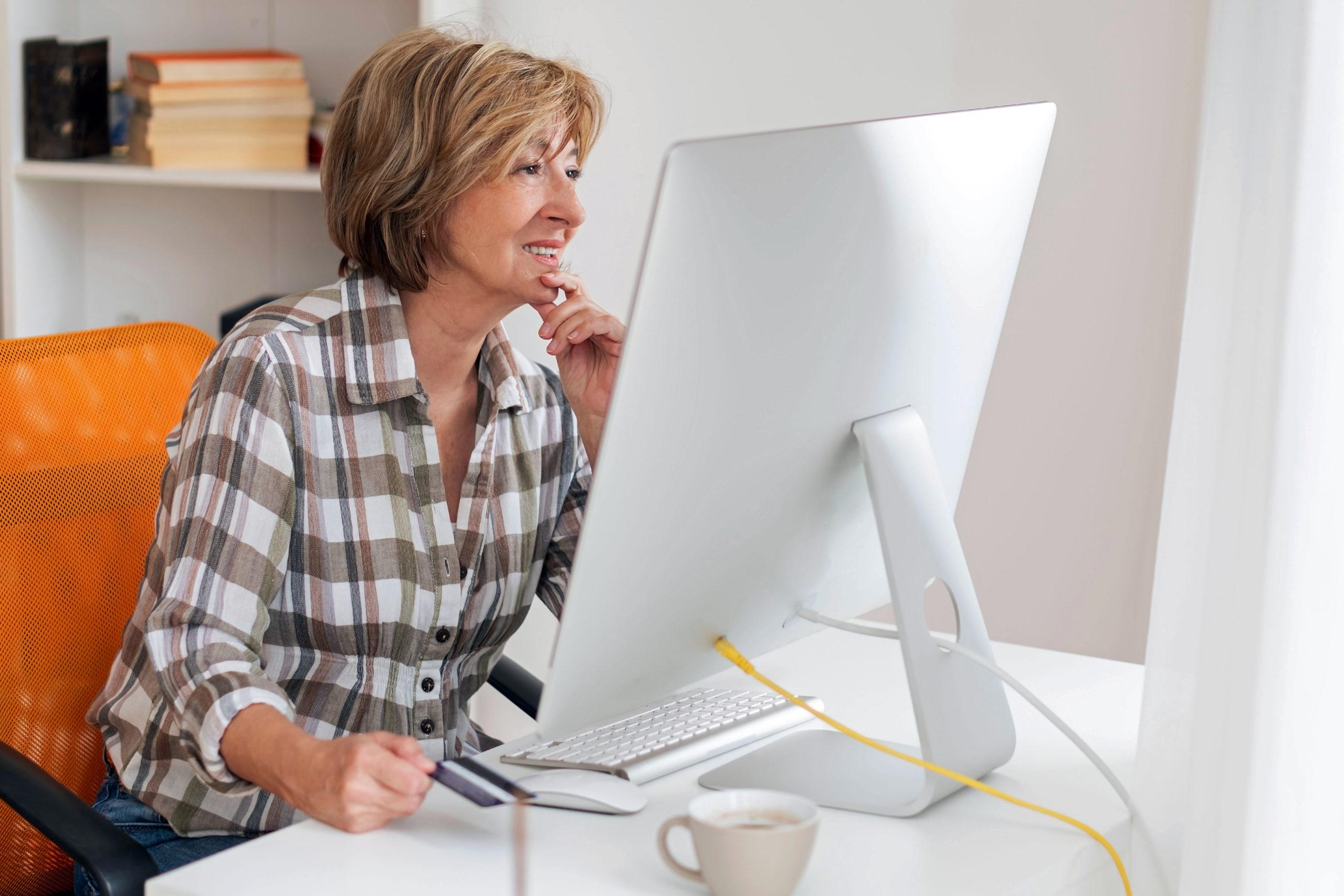Ältere Frau am Computer erkennt Online-Gefahren