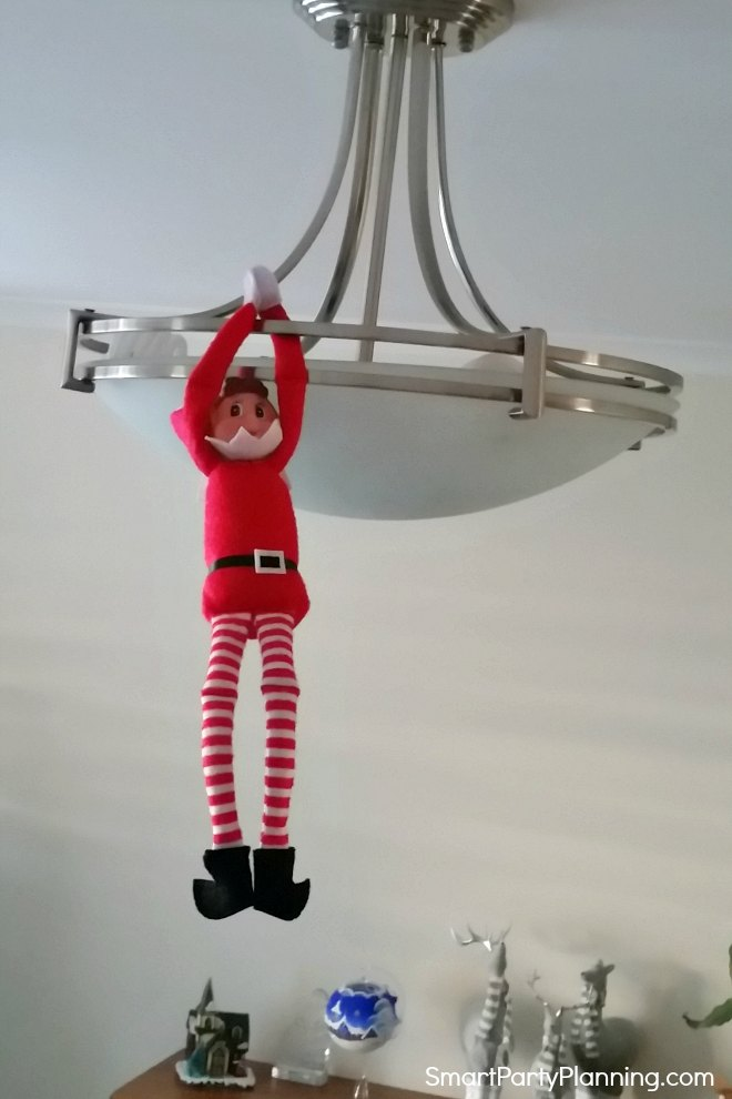 Elf on the shelf hangs from a light shade
