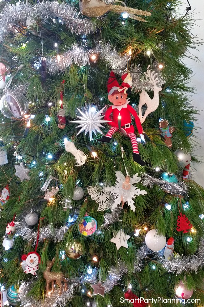elf on the shelf sits in the Christmas tree