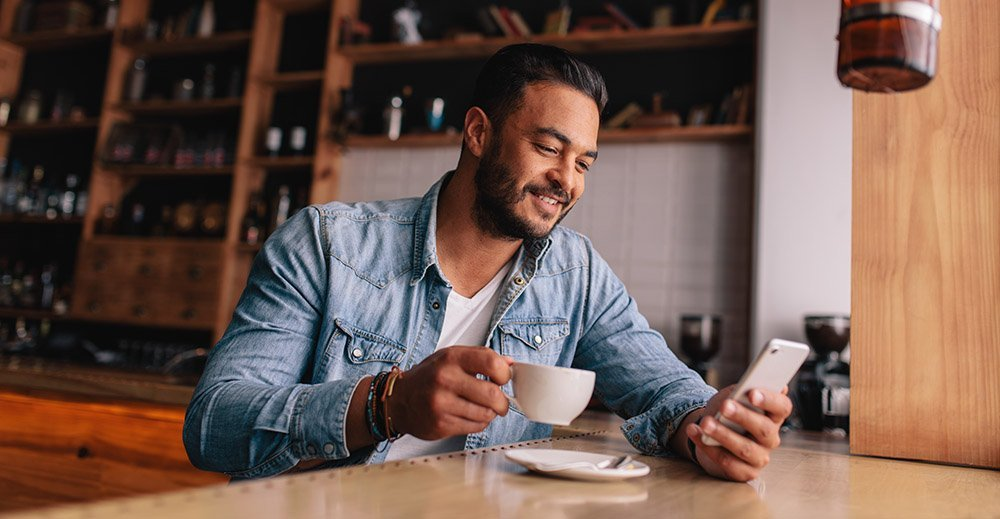 Handsome young man having coffee and using mobile phone marketing personalization strategy