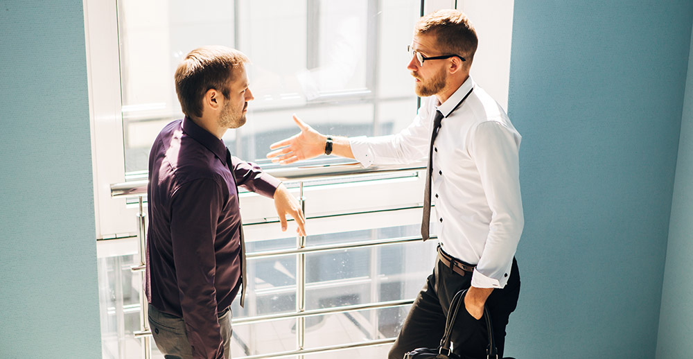two men talking in the lobby of the office handling employee complaints