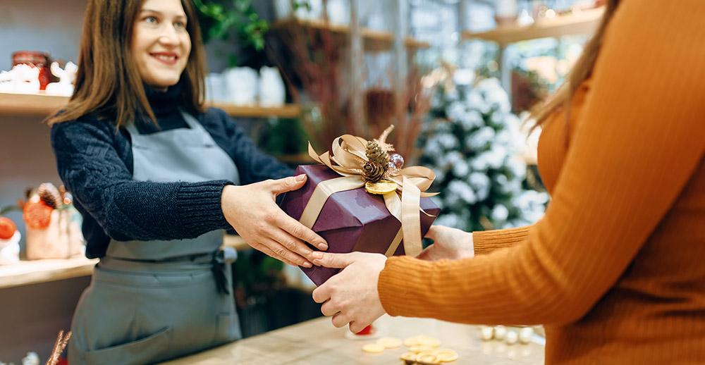 Female seller gives to customer christmas gift box hiring the best seasonal employees