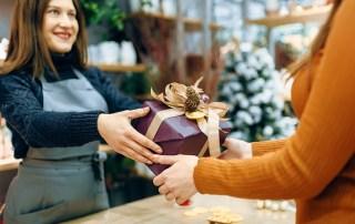 Female seller gives to customer christmas gift box