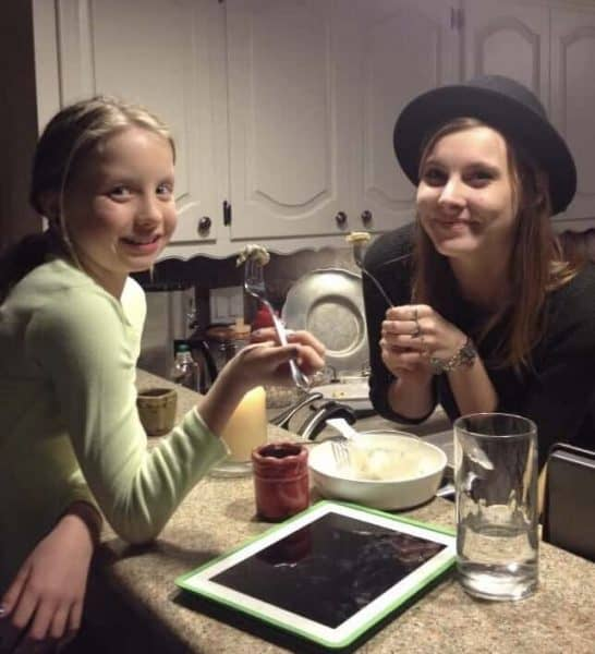 Anecia's daughter and her friend holding forks at a kitchen counter