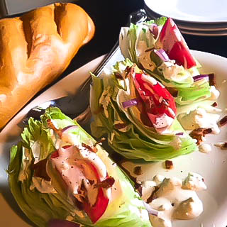 Three slices of wedge salad with sliced tomato, red onion, bacon and blue cheese dressing