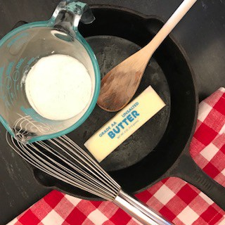 A cup of flour, a stick of butter, a whisk and a wooden spoon in a cast iron skillet