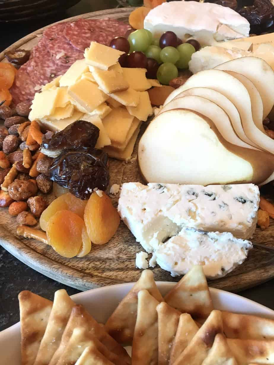 Cheese board with variety of cheeses, nuts, dried fruit and olives on a wooden board
