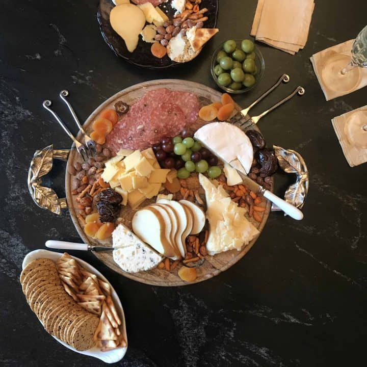 Variety of cheese, meats and nuts on wooden board