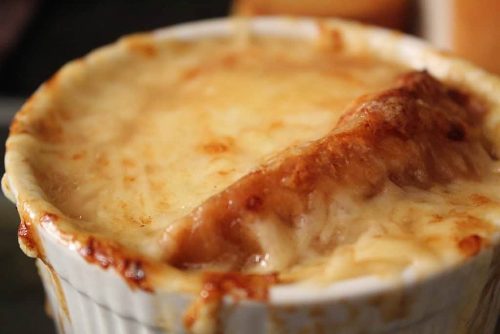 French Onion Soup topped with cheese in white ramekin