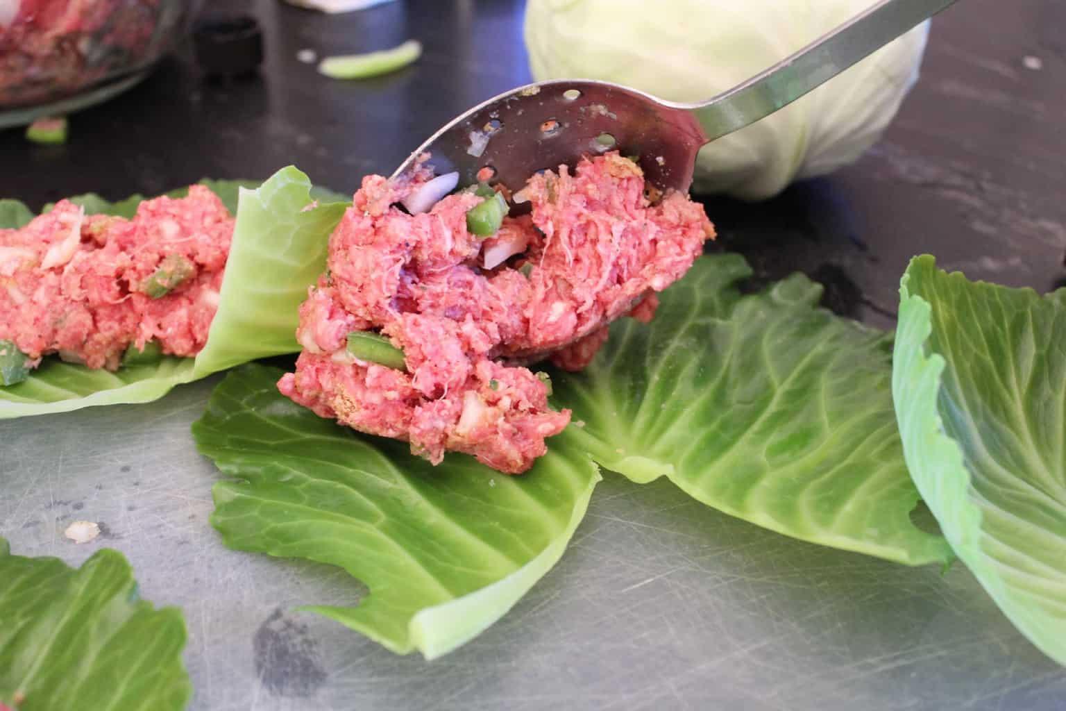 Meat mixture being spooned onto leaf.