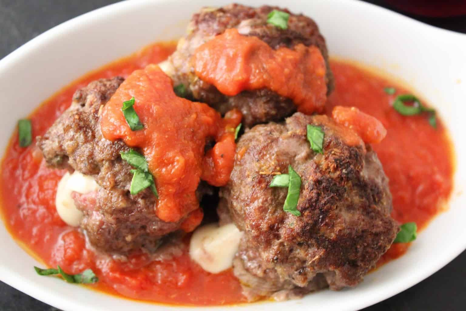 Three Mozzarella stuffed meatballs in red sauce, topped with fresh bail