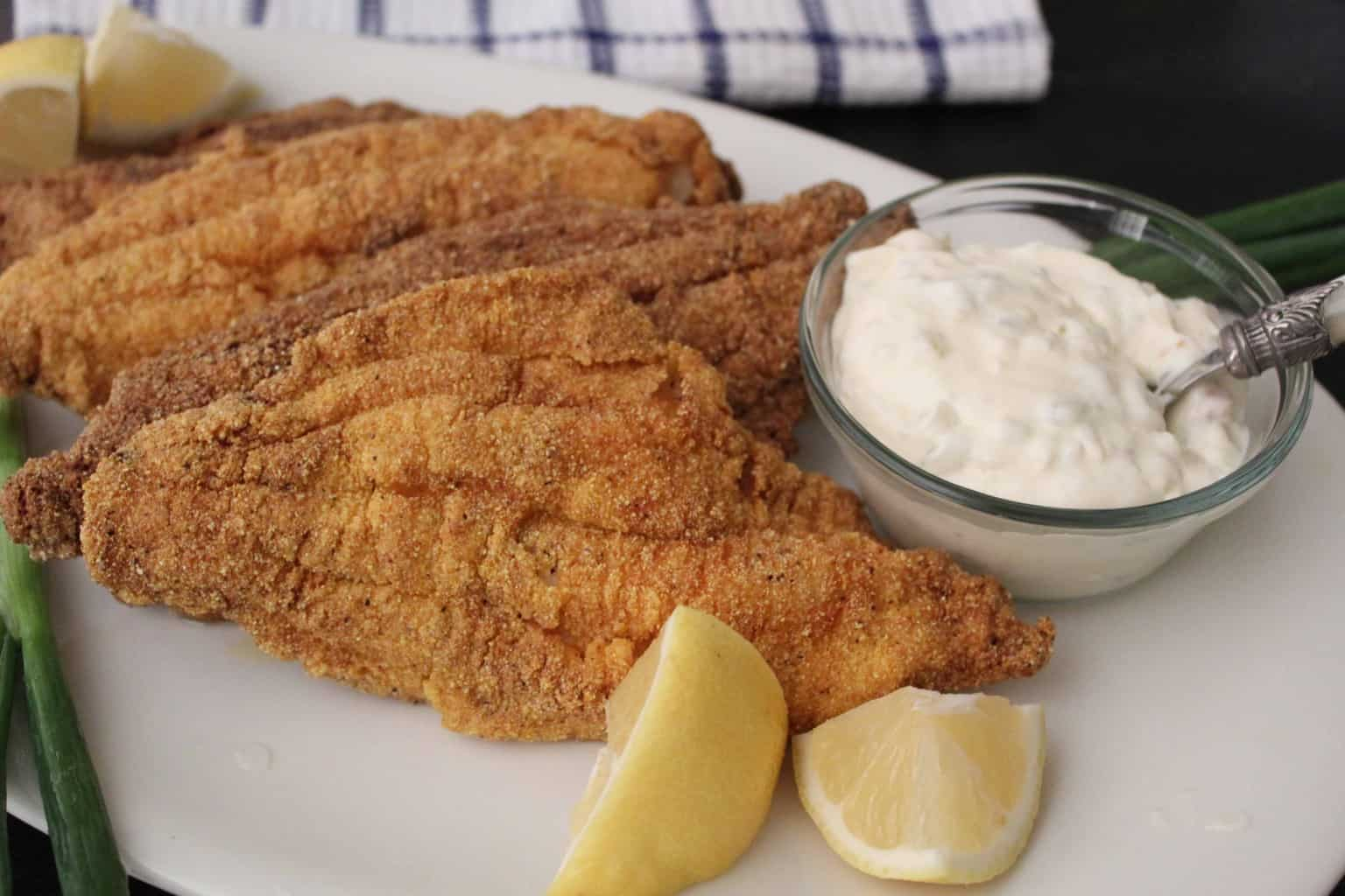 Fried catfish with a side of tartar sauce and lemon on white plate