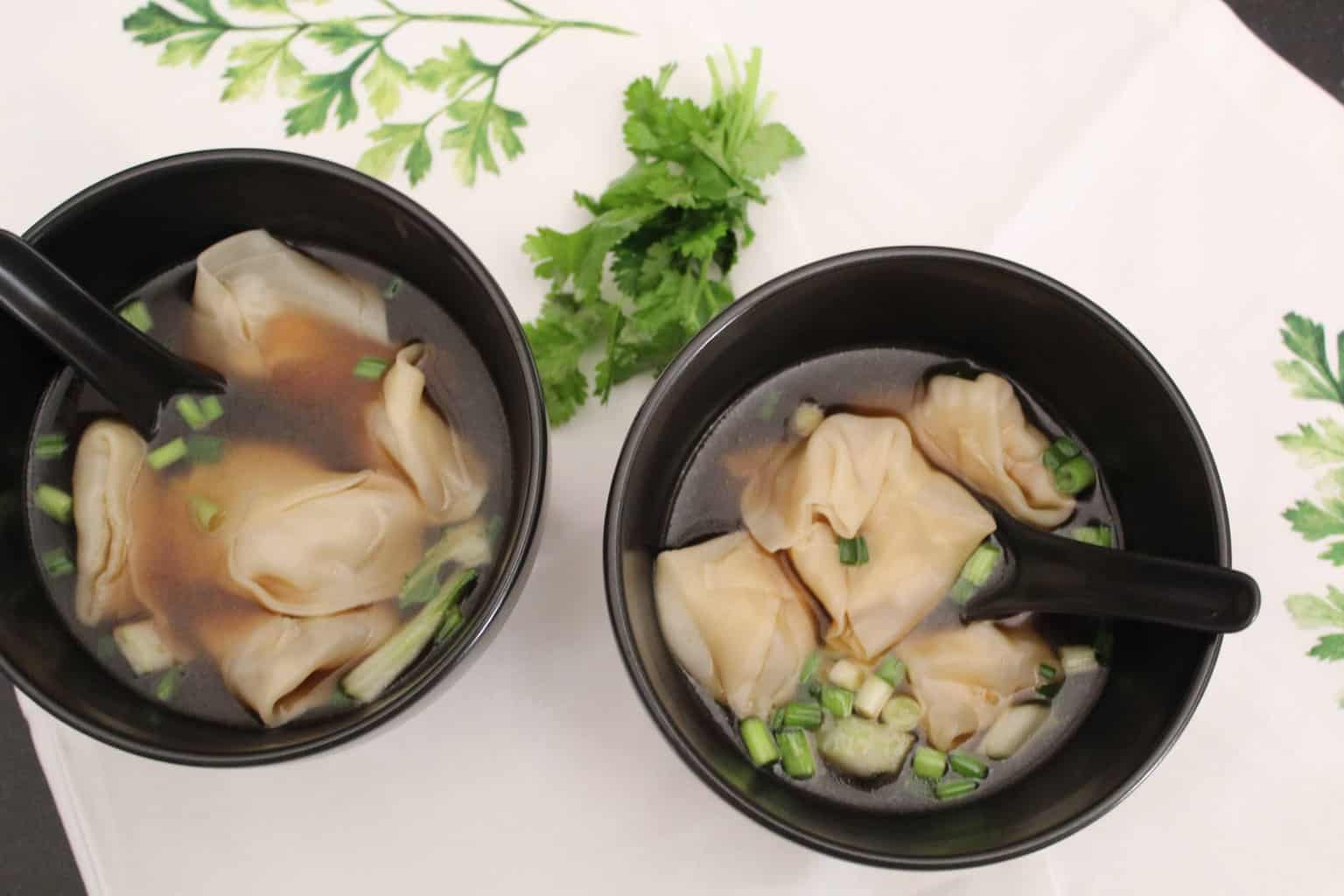 Two Bowls of Won Ton Soup on white tablecloth.