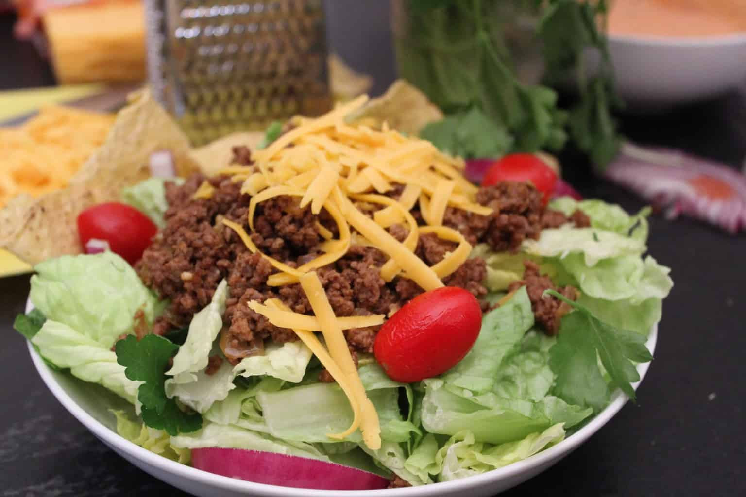 Weeknight Taco Salad garnished with taco meat, red onion, cherry tomatoes and shredded cheese