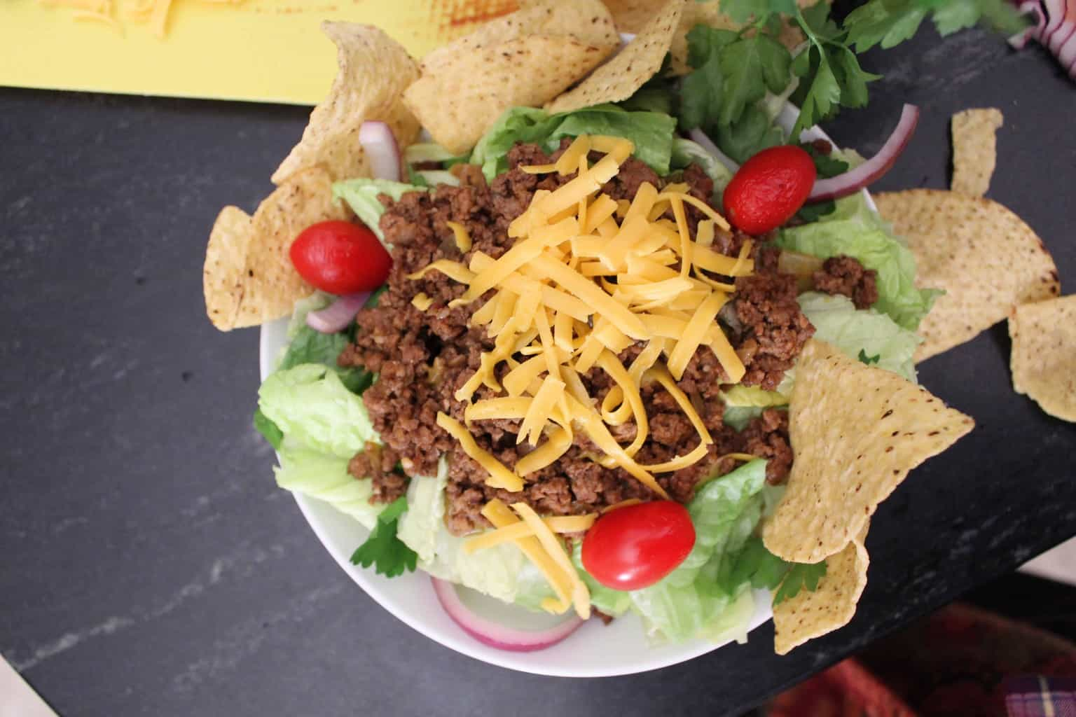 Taco Salad garnished with cheddar cheese, cherry tomatoes and tortilla chips