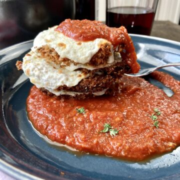 Crispy eggplant parmesan rounds stacked, topped with sauce and cheese