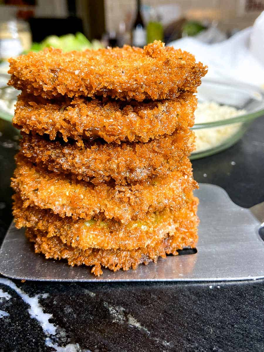 Crispy fried eggplant rounds stacked on stainless spatula
