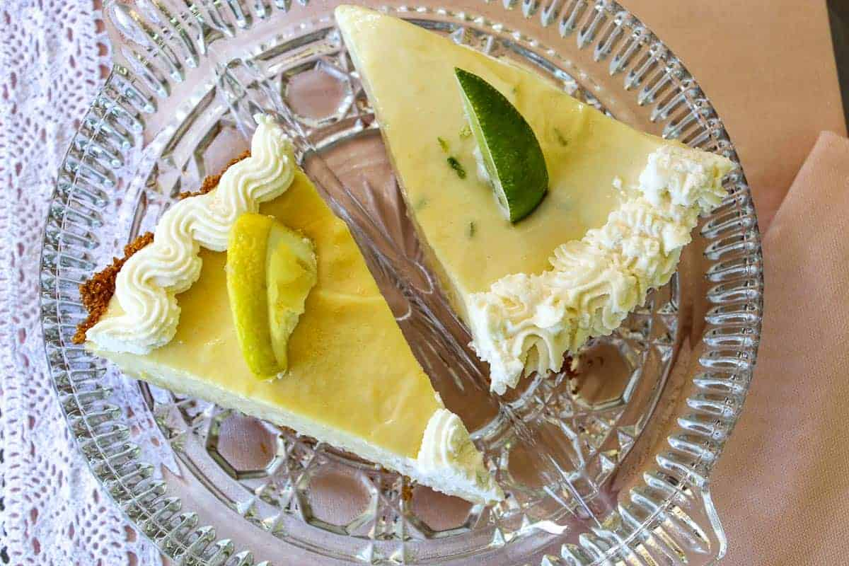 Two slices of lemon and key lime icebox pies on crystal plate