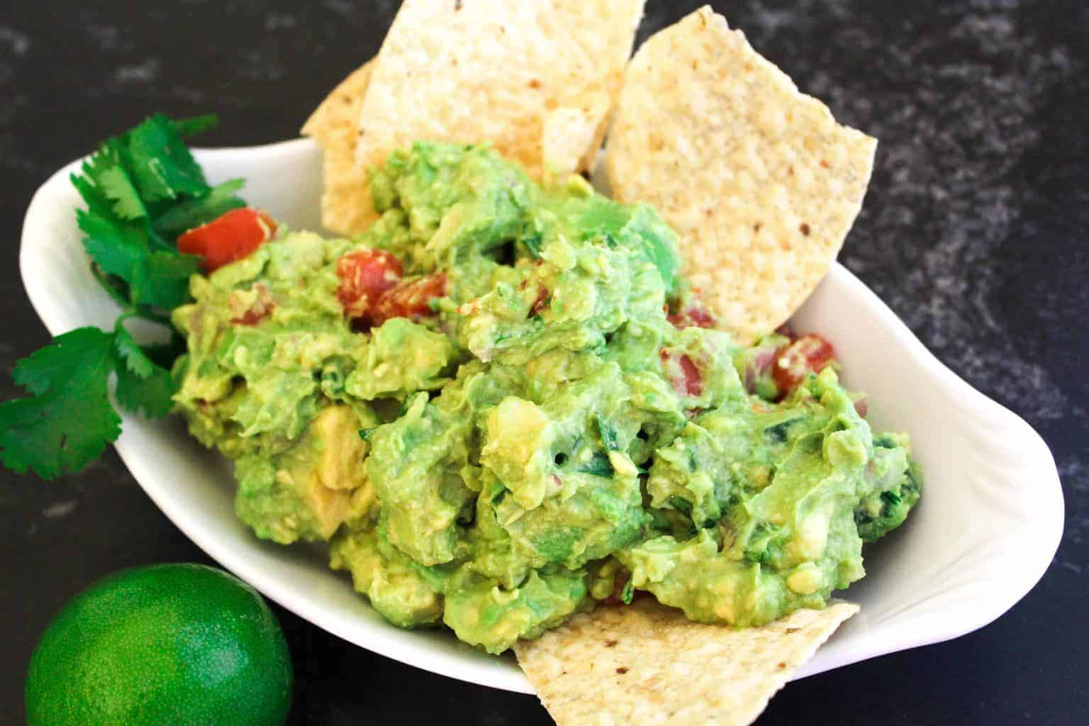 Guacamole in oval serving dish garnished with cilantro and chips.