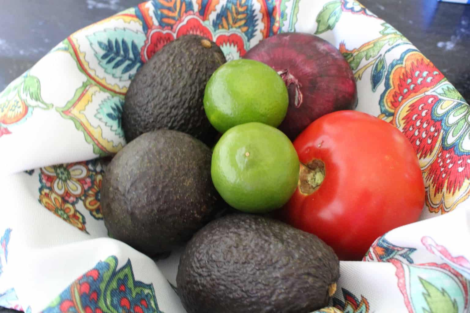 Avocados, limes, tomato and red onion in decorative bowl.