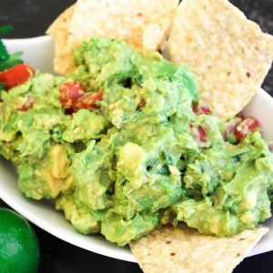 Guacamole in a white serving bowl with chips.