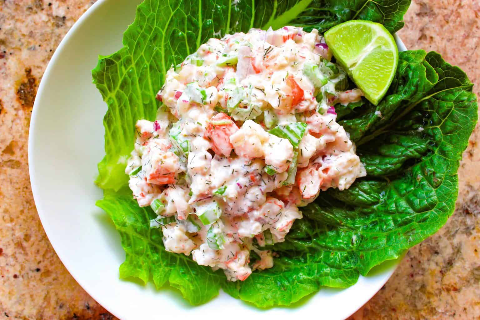Cold Shrimp Salad on a bed of romaine lettuce garnished with a lime