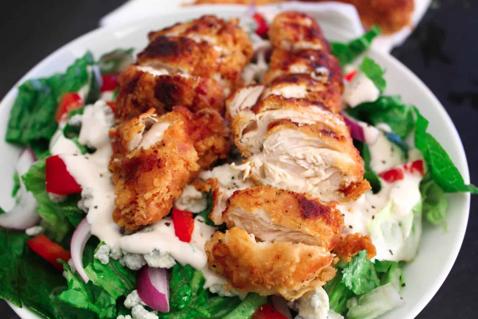 Fried chicken slices over green salad