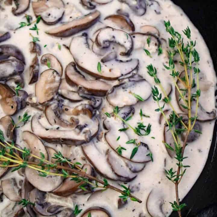 Mushroom cream sauce garnished with thyme sprigs in black skillet