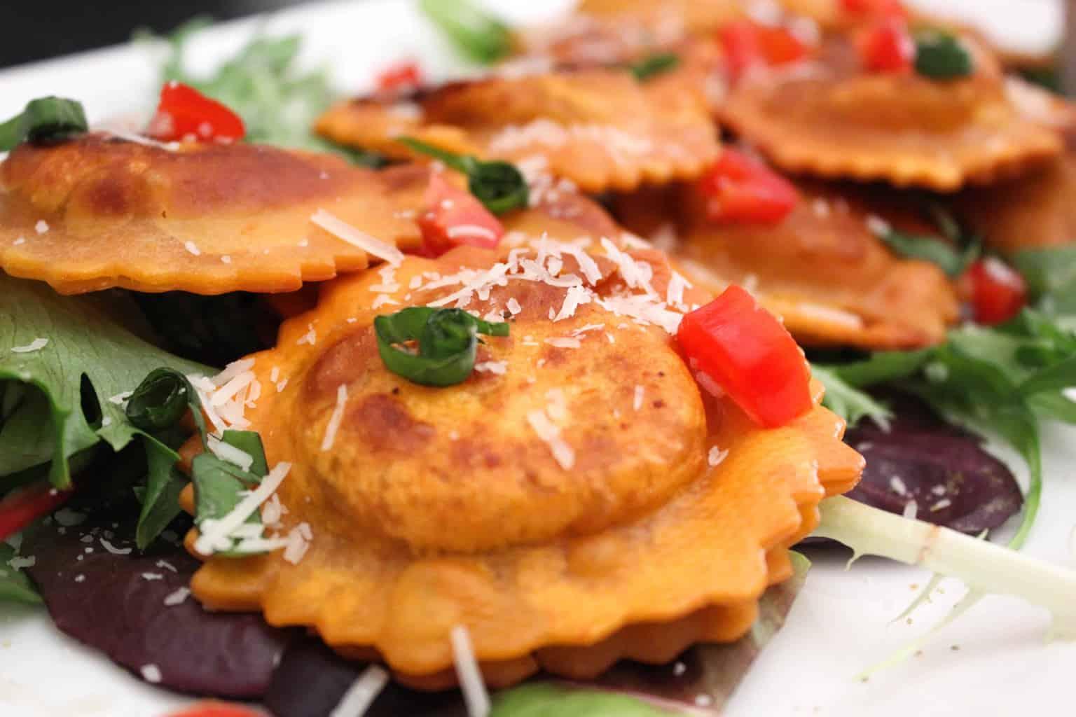 Close up fried ravioli with parmesan cheese, tomato and basil garnish