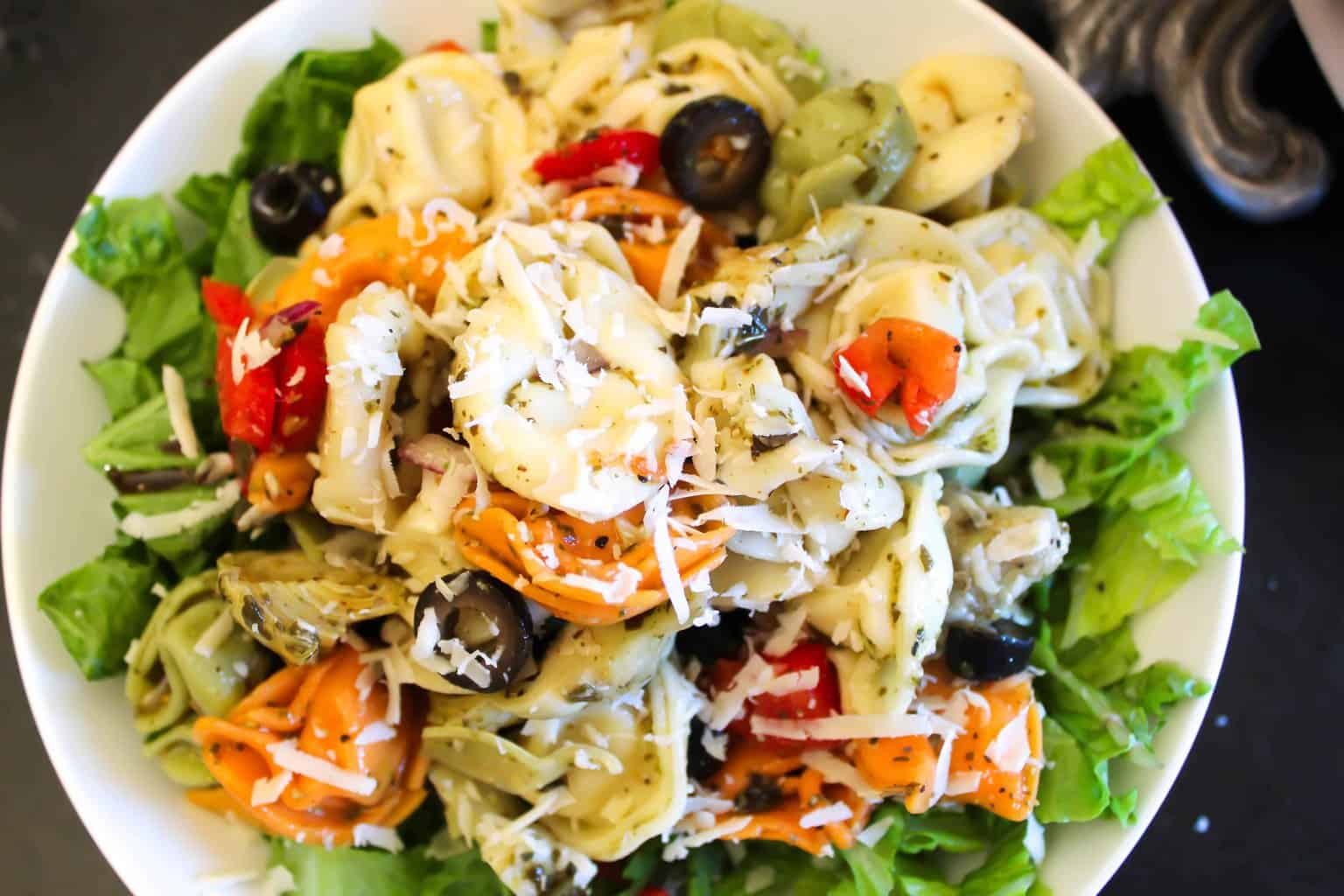 Tortellini Pasta Salad in a white bowl on a bed of green lettuce