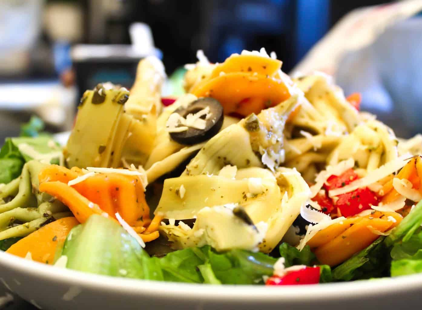 Tortellini Pasta Salad garnished with shredded mozzarella cheese