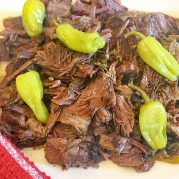 Shredded Mississippi Pot Roast with pepperoncini on white plate