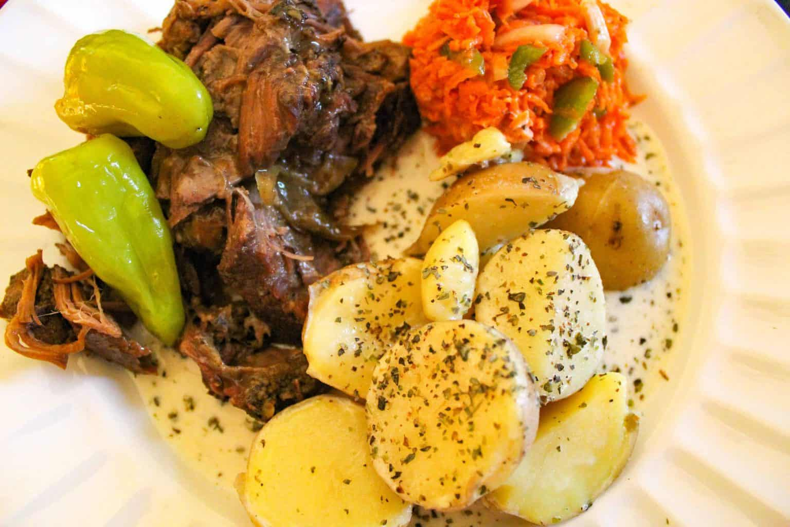 Mississippi Pot Roast with Gravy, cream potatoes and carrot slaw on white plate
