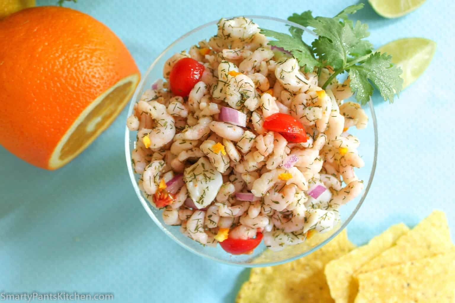 orange ceviche in glass bowl garnished with dill and cherry tomatoes