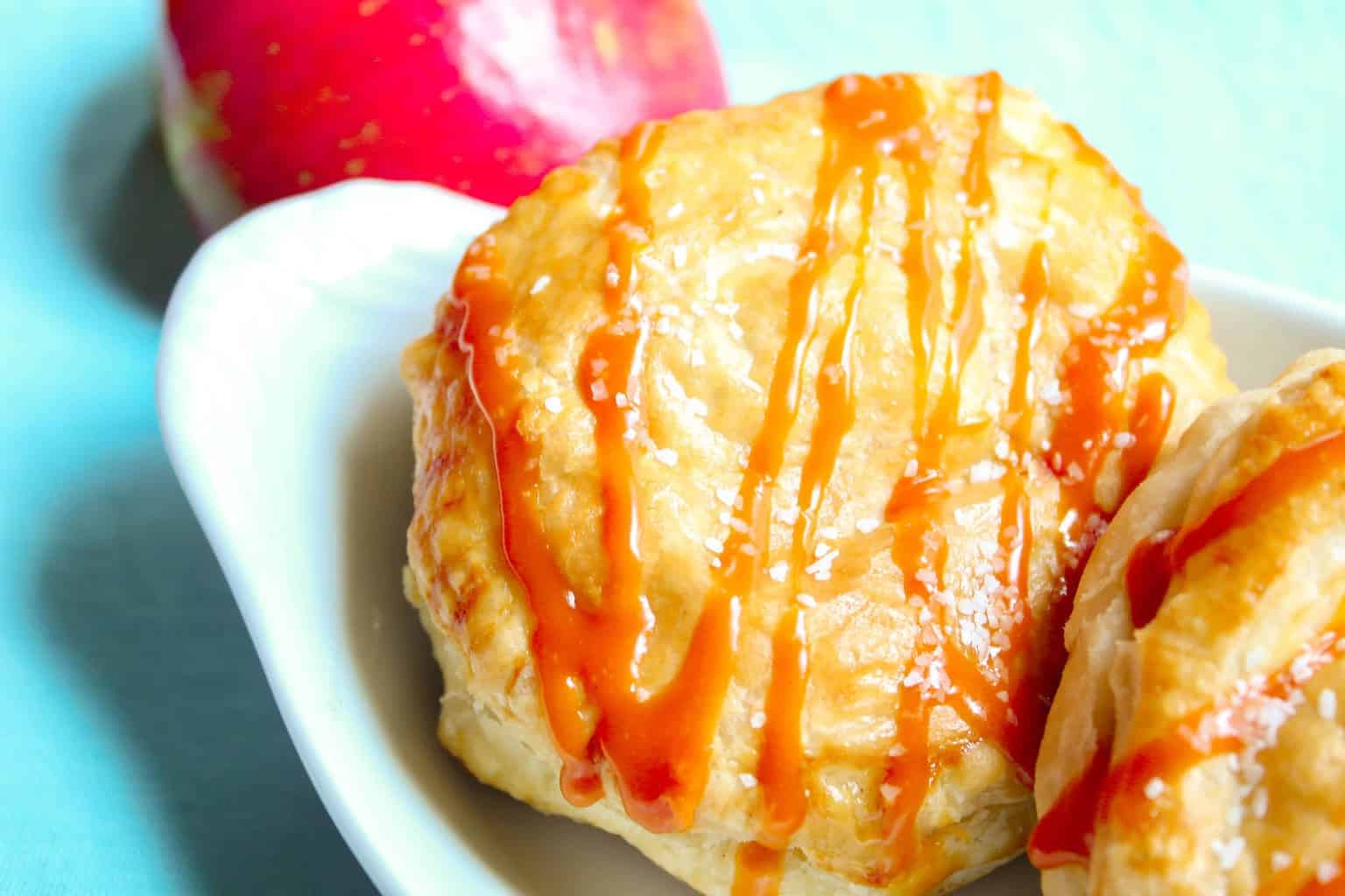 Puff pastry drizzled with caramel sauce with red apple on the side