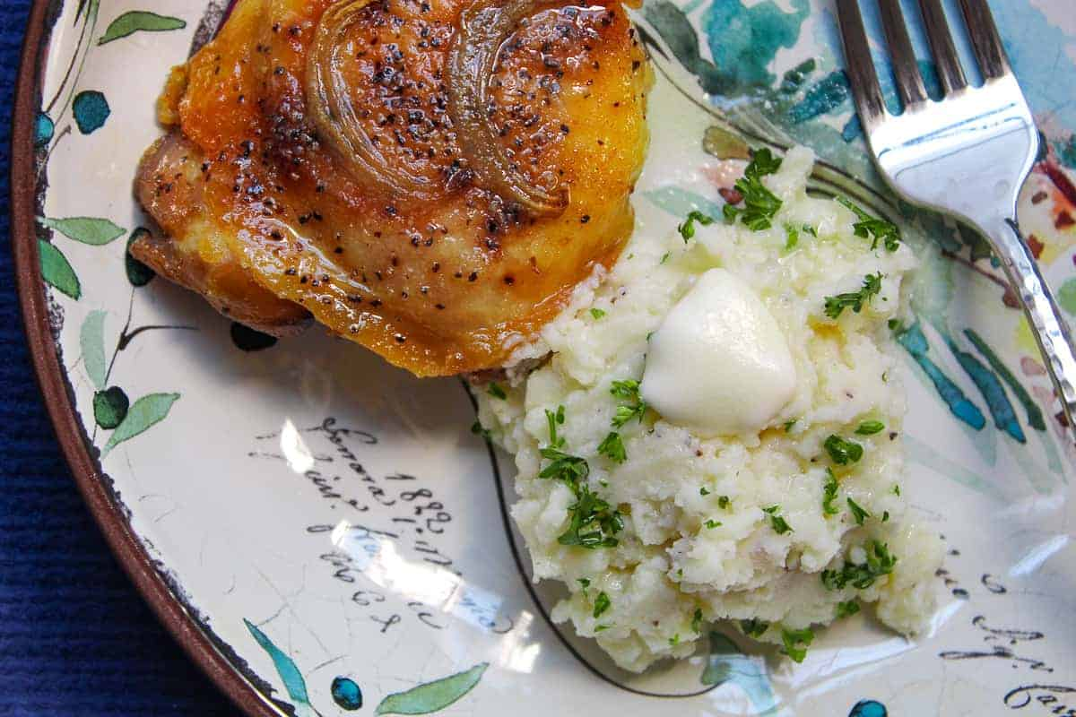 Oven baked chicken thigh and mashed potatoes on decorative plate