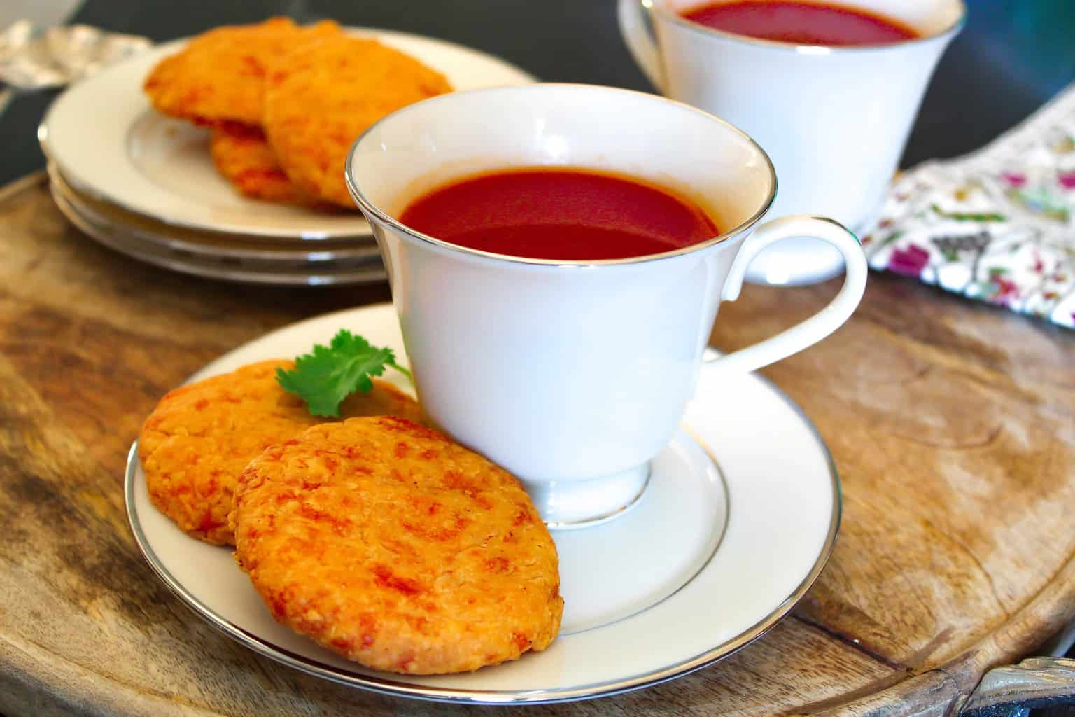 Non-Alcohol Southern Tomato Aperitif in a white china cup with two cheddar wafers on the saucer