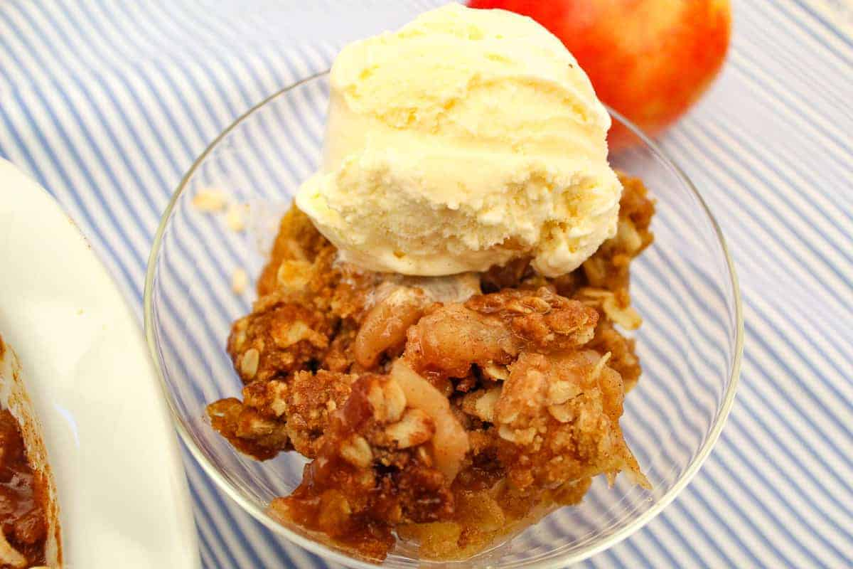 Apple crisp in clear parfait dish with a scoop of vanilla ice cream on top