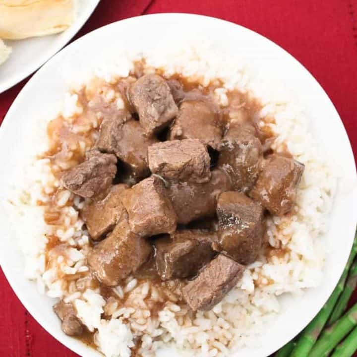 Beef tips and gravy over white rice on white plate
