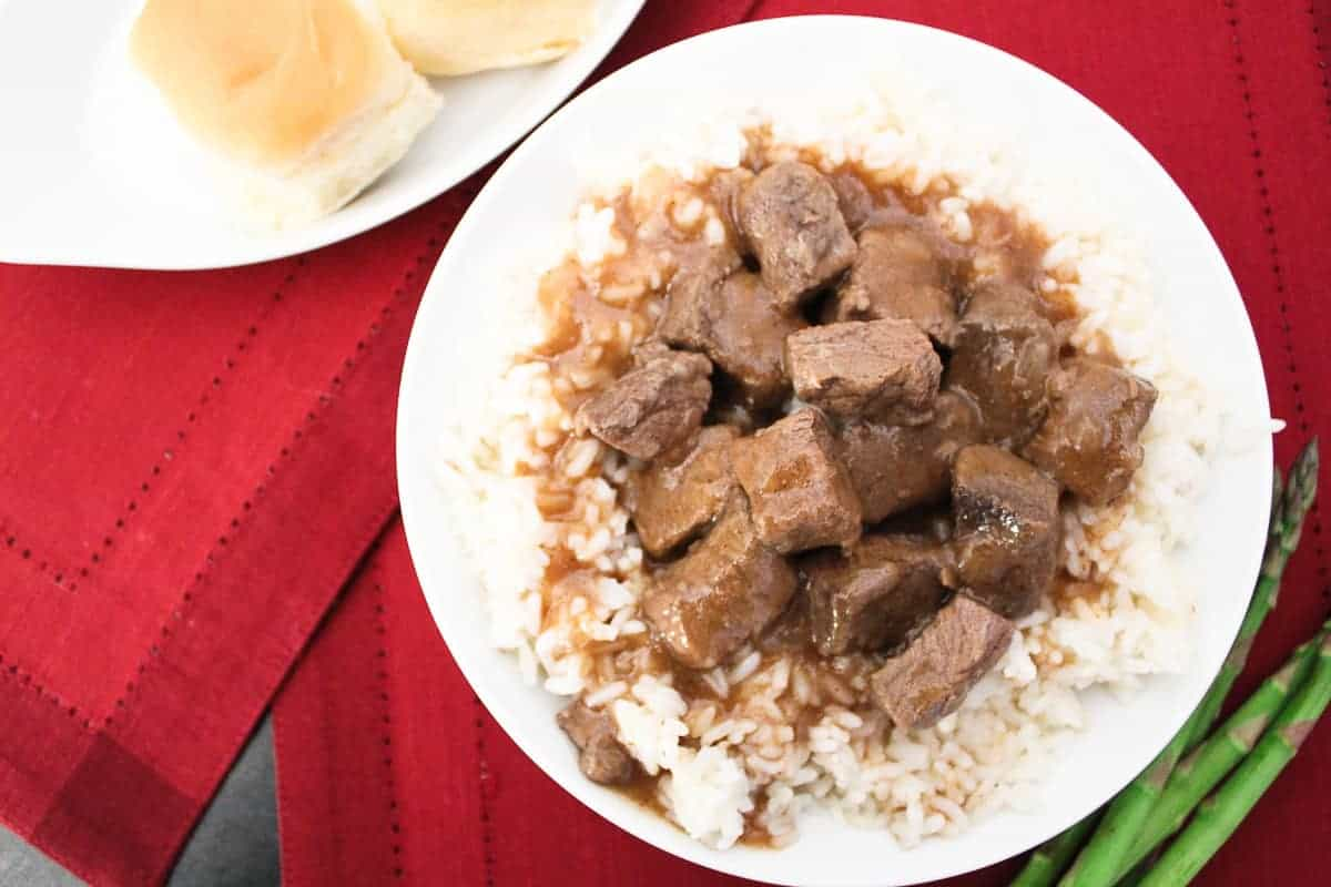 Beef tips and gravy with white rice, a side of rolls and asparagus on the side