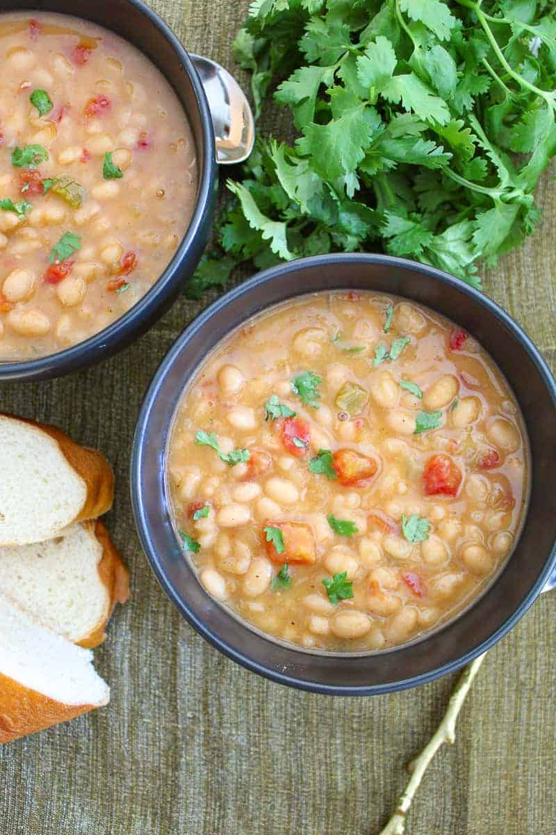 Southwestern Navy Bean soup in two black bowls garnished with cilantro