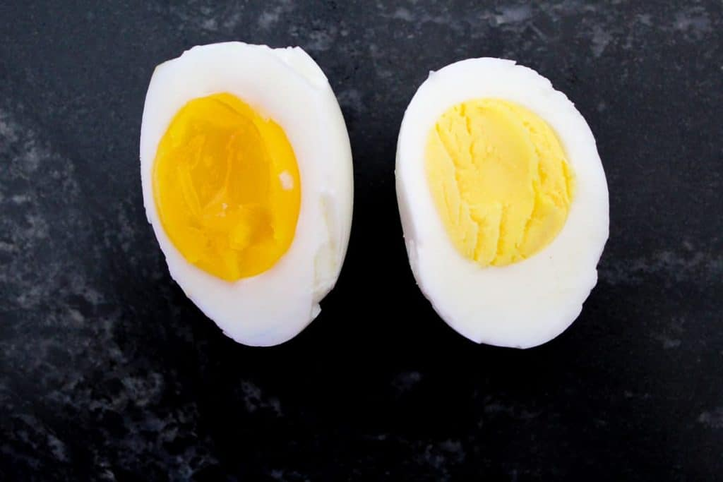 Hard and soft boiled eggs cut in half to show the difference in cooking times
