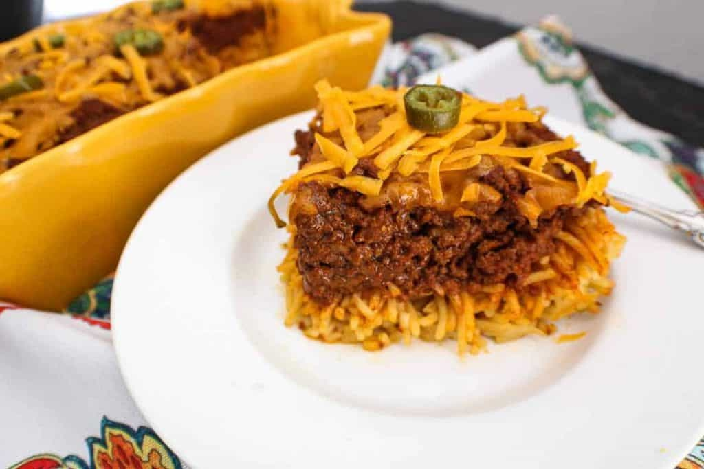 Slice of chili spaghetti pie on a white plate