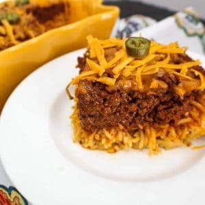 Slice of chili spaghetti pie on a white plate
