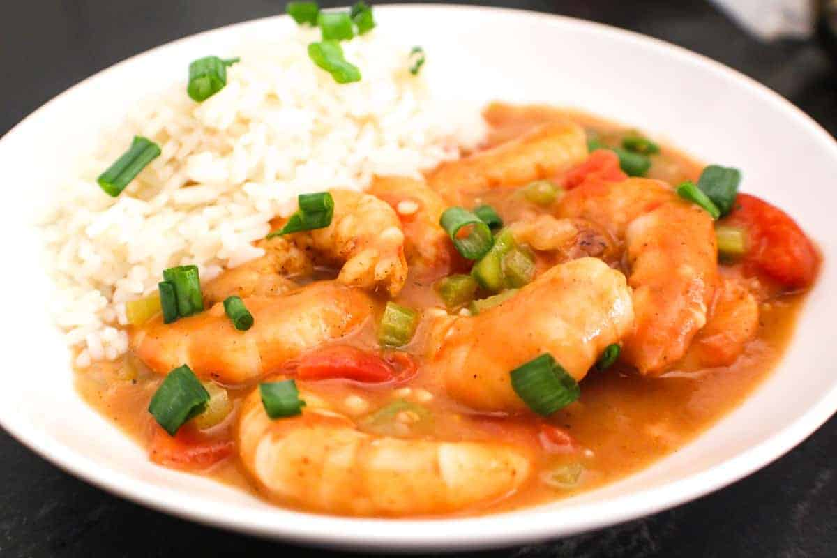 Close up image of Shrimp Etoufee and a side of rice garnished with green onions