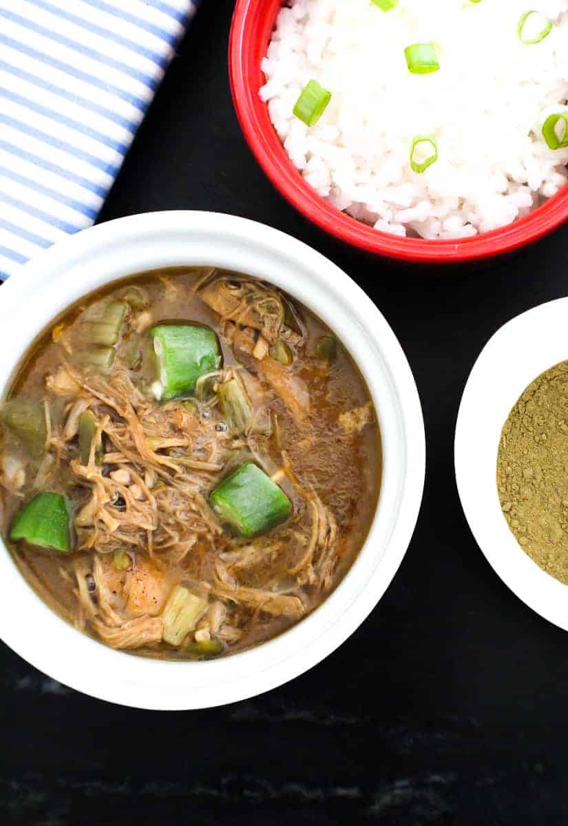 Bowl of gumbo with a side of rice and file powder