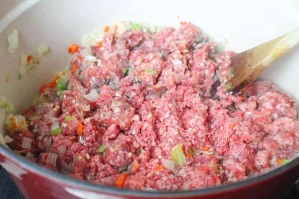 Ground beef added to vegetables in stockpot