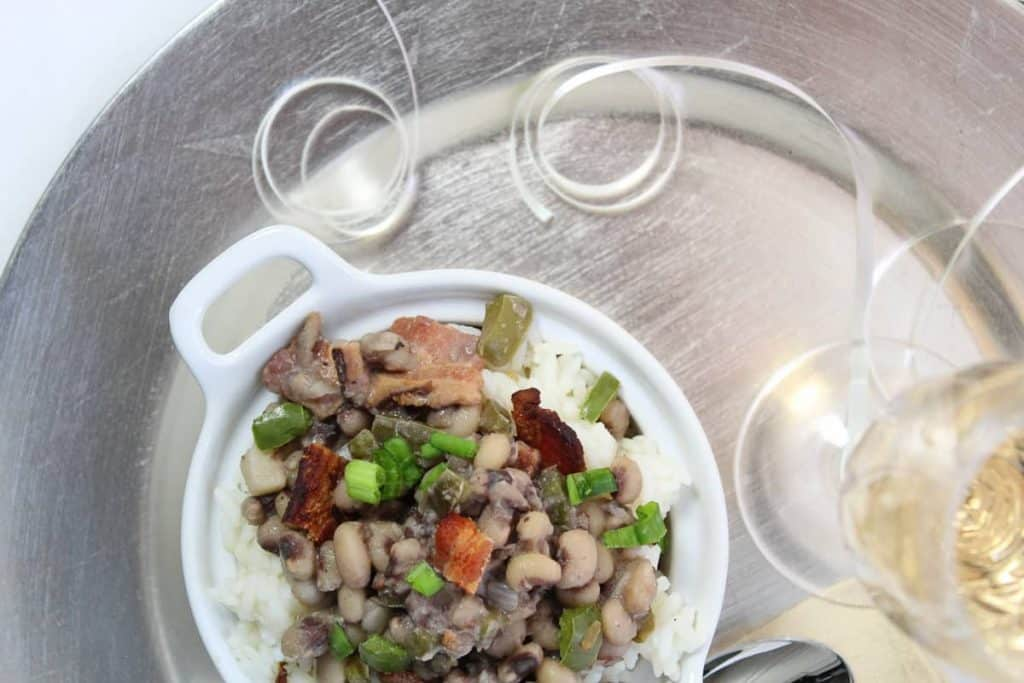 bowl of easy hoppin' john next to glass of champagne